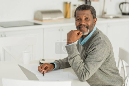 Photo for Smiling african american man looking at camera while sitting at table near laptop - Royalty Free Image