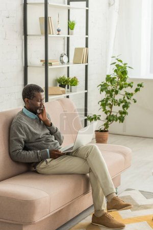 Photo for Thoughtful african american man sitting on sofa in living room and using laptop - Royalty Free Image