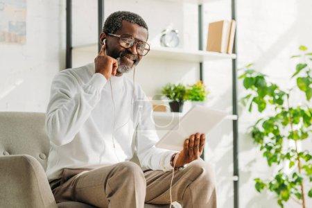 Photo pour Homme afro-américain joyeux écouter de la musique dans les écouteurs et en utilisant une tablette numérique - image libre de droit