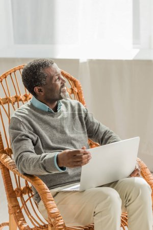 cheerful african american man sitting in wicker chair with notebook and looking away
