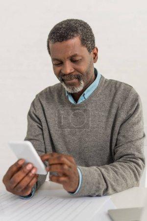 homme afro-américain âgé assis à table et utilisant un smartphone