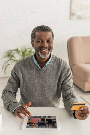cheerful african american man holding credit card and using digital tablet with booking app on screen