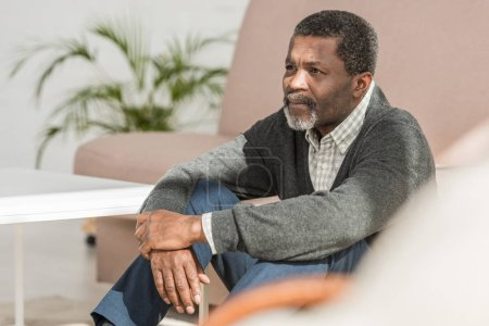 Photo for Depressed african american man sitting on floor at home and looking away - Royalty Free Image