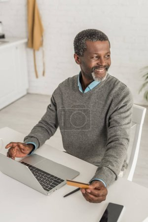 Photo for Cheerful african american man looking away while sitting near laptop and holding credit card - Royalty Free Image