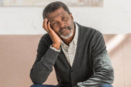 Photo pour Rêveur afro-américain assis sur le canapé à la maison et regardant la caméra - image libre de droit