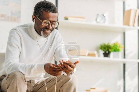 Photo pour Homme afro-américain joyeux en utilisant smartphone tout en écoutant de la musique dans les écouteurs - image libre de droit