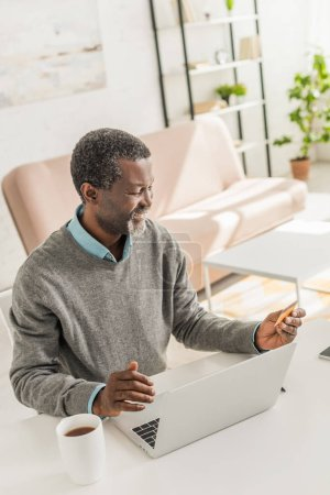 Photo for Cheerful african american man sitting near laptop and holding credit card - Royalty Free Image