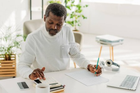 Photo for Serious african american man sitting at table near utility bill and calculating expenses - Royalty Free Image