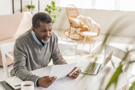 Photo for Selective focus of senior african american man looking at utility bill while sitting near laptop - Royalty Free Image