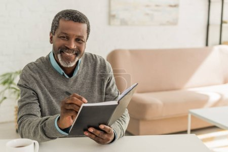 cheerful african american man smiling at camera while holding notebook