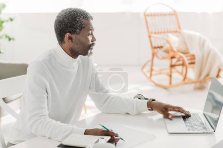 Photo for Serious african american man using laptop while calculating communal expenses - Royalty Free Image