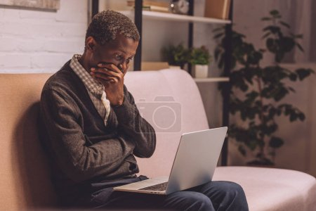 Photo for Upset african american man sitting on sofa and looking at laptop - Royalty Free Image
