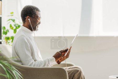 cheerful african american in earphones sitting in armchair and using digital tablet