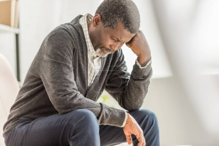Photo pour Selective focus of depressed african american man sitting with bowed head - image libre de droit