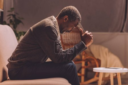 Photo for Depressed african american man sitting on sofa at night and holding photo frame near head - Royalty Free Image
