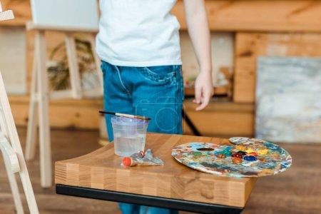 Photo pour Vue recadrée d'un enfant debout près d'une table en bois avec des peintures gouache - image libre de droit