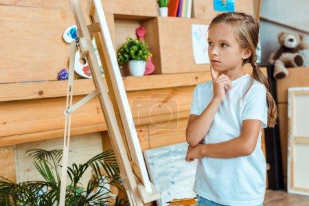 Foto de El niño penoso que mira el easel en la escuela de arte - Imagen libre de derechos