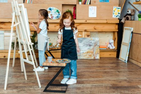 Foto de Pete redhead kid sostener pincel cerca de pinturas coloridas de dolor de garganta y niños. - Imagen libre de derechos