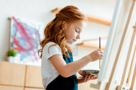 Foto de Enfoque selectivo de la paleta de agarre de cabezal rojizo lindo y pincel de pincel cerca del easel. - Imagen libre de derechos