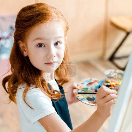 Photo pour Foyer sélectif de mignon rousse enfant tenant pinceau et regardant la caméra - image libre de droit