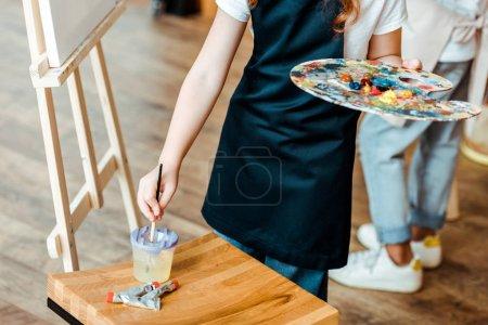 Foto de Vista panorámica de la paleta y el pincel cerca del niño en la escuela de arte. - Imagen libre de derechos