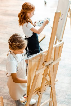 selective focus of child painting near redhead kid in art school