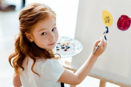 Foto de Enfoque selectivo de la linda pintura de cabezal rojo en la escuela de arte - Imagen libre de derechos