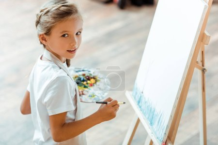 selective focus of cute kid holding multicolored palette in art school