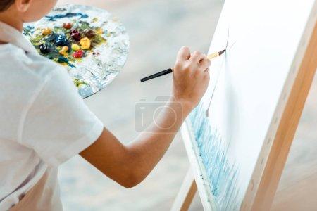 Photo pour Vue recadrée de l'enfant haletant sur toile à l'école d'art - image libre de droit