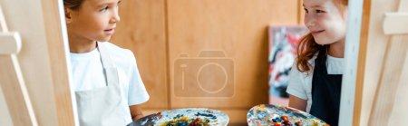 Foto de Foto panorámica de niños con paleta de colores y mirándose unos a otros. - Imagen libre de derechos