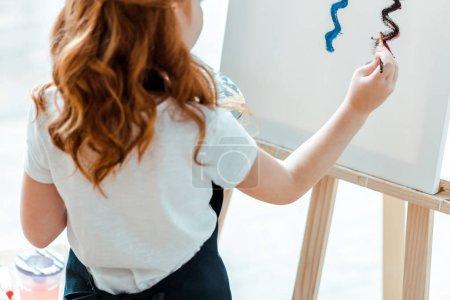 Photo pour Crochet vue d'un enfant rouge peinture sur toile dans une école d'art - image libre de droit