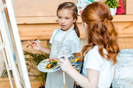 Photo for Selective focus of cute kid looking at easel near redhead child in art school - Royalty Free Image
