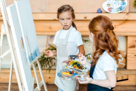 Photo for Selective focus of adorable kid looking at redhead child near easels in art school - Royalty Free Image