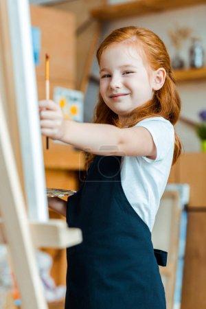 Photo pour Foyer sélectif de la rousse positive enfant tenant pinceau - image libre de droit