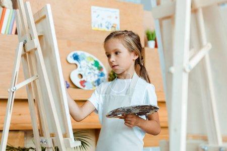 Foto de Enfoque selectivo de la pintura infantil linda en la escuela de arte - Imagen libre de derechos