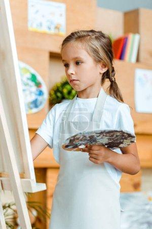 Photo pour Foyer sélectif de la peinture adorable enfant à l'école d'art - image libre de droit
