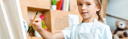 Foto de Foto panorámica de un chico sonriente sosteniendo el pincel cerca del easel. - Imagen libre de derechos