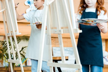 cropped view of kids in aprons standing near easels with palette
