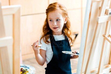 Photo pour Foyer sélectif de gamin rousse mignon tenant la palette et regardant loin - image libre de droit