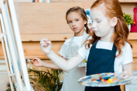 Photo for Selective focus of cute kid looking at redhead child near easel - Royalty Free Image