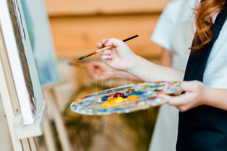 Photo for Cropped view of kids with paintbrushes near canvas - Royalty Free Image