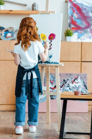 Photo pour Back view of redhead kid painting on canvas - image libre de droit