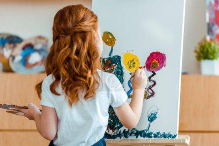 Photo pour Retour de la peinture d'un enfant à tête rouge sur toile dans une école d'art - image libre de droit