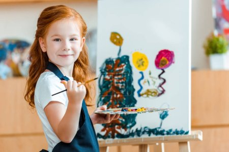 Photo for Smiling redhead child standing near painting on canvas in art school - Royalty Free Image