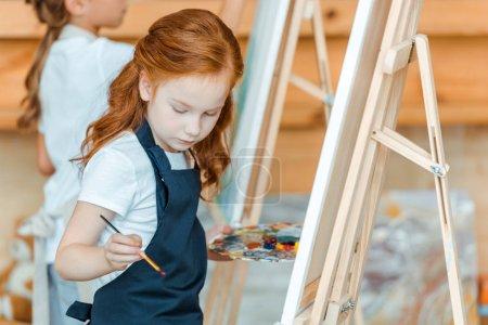 enfoque selectivo de lindo niño de pie y la pintura en la escuela de arte
