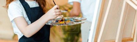 Photo pour Plan panoramique de gamin tenant palette et pinceau près du chevalet - image libre de droit