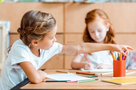 Photo pour Focus sélectif de crayon de couleur pour enfant près d'un enfant à tête rouge - image libre de droit