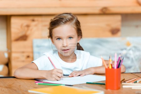 Photo for Selective focus of cute child looking at camera while drawing on paper in art school - Royalty Free Image