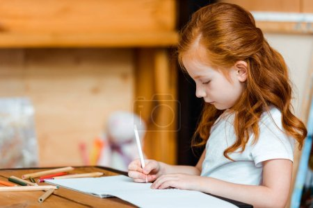 Photo for Cute redhead kid drawing on paper in art school - Royalty Free Image