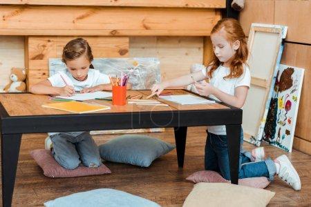 Photo pour De beaux enfants dessinant sur des papiers assis sur des oreillers - image libre de droit